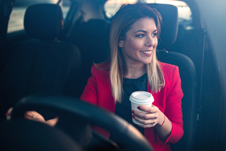 go inside: Woman sipping a coffee while driving a car. Stock Photo