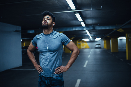 Portret van een vermoeide Afro-Amerikaanse atleet man met zijn handen op de heupen en het luisteren naar muziek in de ondergrondse parkeergarage.