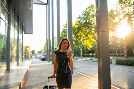 background skype: Beautiful businesswoman texting on a mobile phone while traveling.