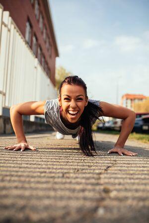 Beautiful young  woman doing push ups outdoors.