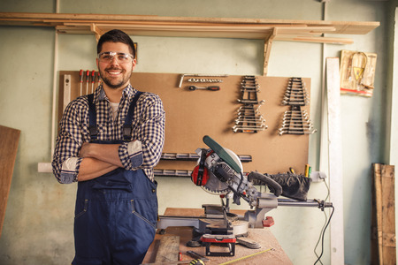 Portrait of smiling young carpenter working in his workshop.