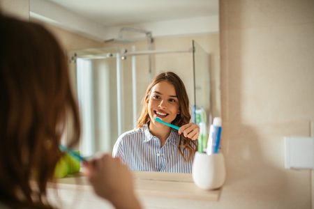 Portrait of beautiful young woman brushing teeth in the bathroom.