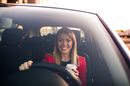 Woman drinking a coffee while driving a car.