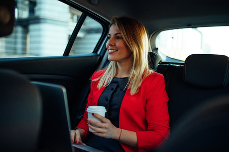 go inside: Beautiful businesswoman using laptop while sitting on a backseat of a car. Stock Photo