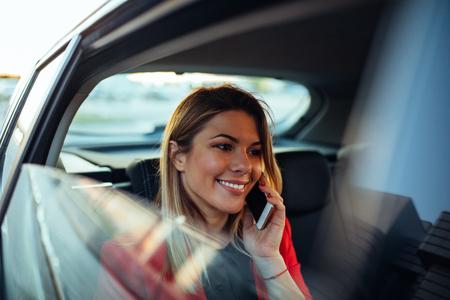 Aantrekkelijke elegante vrouw die op de telefoon spreekt terwijl het reizen door auto.