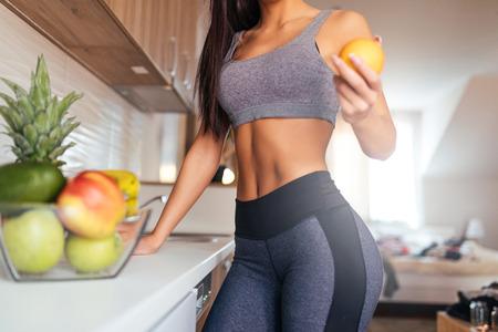 Bebouwd schot van jonge vrouw die fruit voor ontbijt eet. Stockfoto