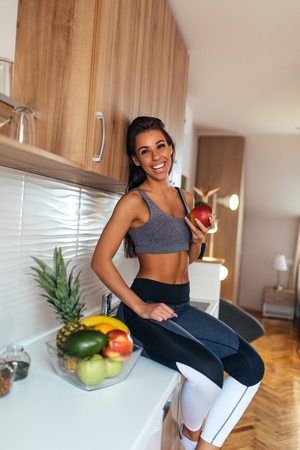 Beautiful young woman eating fruit for breakfast.