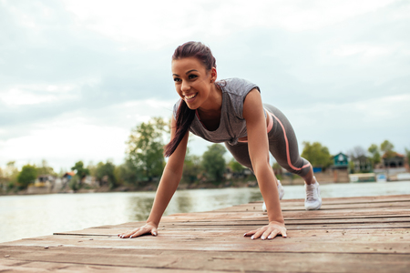 Full length portrait of a smiling athlete woman doing push ups on the deck.
