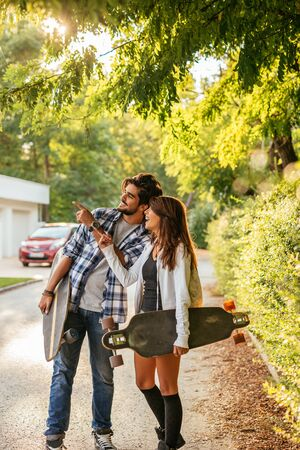 Portrait of young couple enjoying spending time together and holding longboards. 版權商用圖片