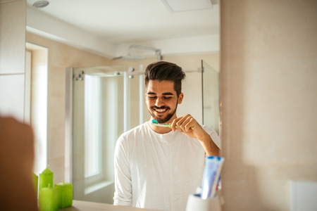 Portrait of handsome young man brushing teeth in the bathroom.