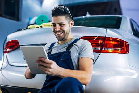 Portrait of a smiling young auto mechanic using digital tablet while leaned on the car.