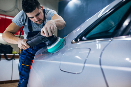 Portrait of a young serviceman polishing a car. Banco de Imagens