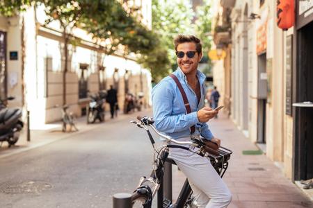 잘 생긴 세련 된 남자 texting 전화 및 도시에서 자전거를 운전.