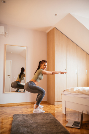 Young attractive woman doing squats at home.