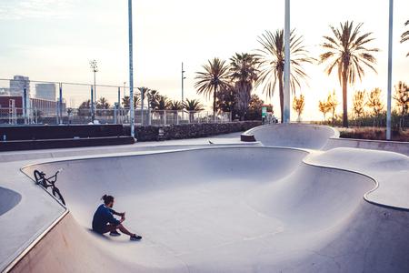 スケート公園でリラックスしながら携帯電話を使用して若い男の写真。