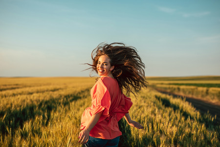 Photo of a young woman running in the field.