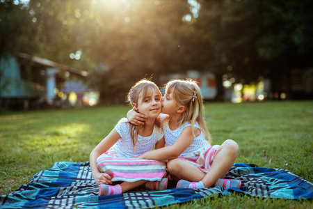 Two sisters sharing love while sitting on a grass in the park.