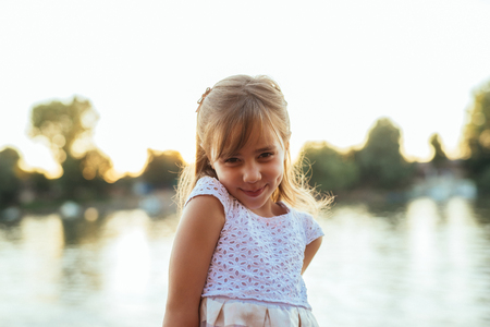 Close up portrait of a smiling girl standing near the river. Imagens
