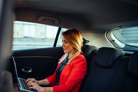 Photo of a young business woman using laptop while sitting in the car.
