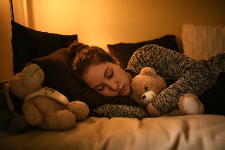 drowsy: Shot of a young teenage girl sleeping with a teddy bear.