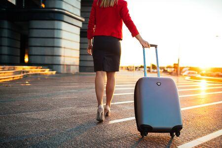 屋外のスーツケースを引いてよく服を着てビジネス ・ ウーマンの肖像画。 写真素材