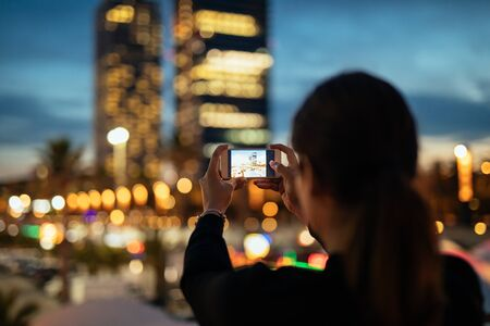 capture the moment: Young woman capturing city at night with mobile phone.
