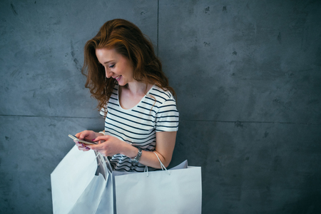 Young girl holding shopping bags and texting on the phone.
