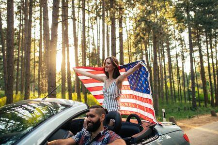 차에 타고있는 동안 미국 국기를 들고 젊은 여자의 총. 스톡 콘텐츠