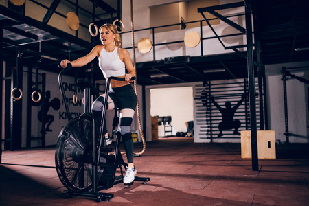 Beautiful woman training on the exercise machine in the gym.
