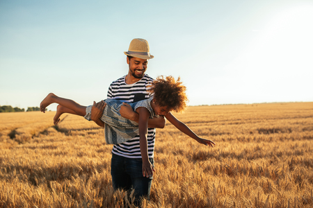 그의 딸 황금 밀밭에서 놀고 젊은 아프리카 계 미국인 아버지의 총. 스톡 콘텐츠