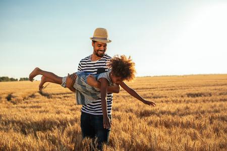 Ontsproten van een jonge Afrikaanse Amerikaanse vader die met zijn dochter op de gouden tarwegebieden speelt.