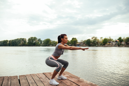 Portrait of an athlete woman doing squats outdoors by the lake.