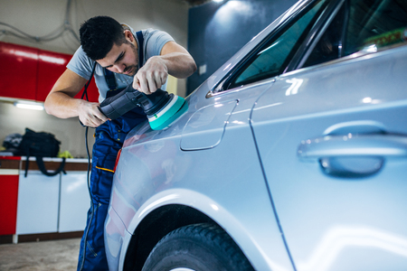 Portrait of a young serviceman polishing a car. Stock Photo
