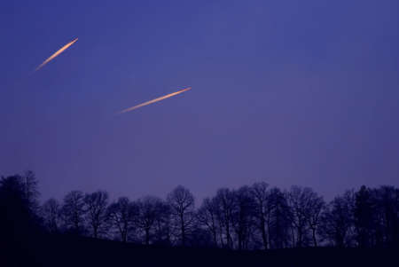 silhoutted: The contrails of two jetplanes richly illuminated by the golden rays of the setting sun agains a darkening winter sky with a row of silhoutted trees. Stock Photo