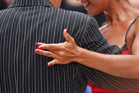 seductive couple: Female hand on the back of a pin striped suit of a tango couple in Buenos Aires, Argentina.
