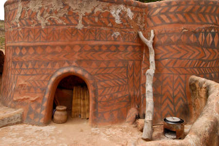 Adboe hut wall in Tiebele, Burkina Faso with traditional tribal painting photo