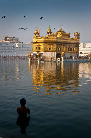 Golden Temple in Amritsar, the holiest sikh temple with a Sikh man taking a morning dip and praying. photo