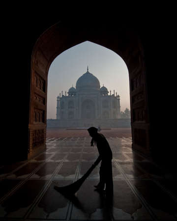 The famous Taj Mahal photographed from the adjacent mosque with a man sweeping the floor. photo