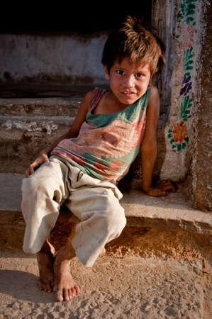 bambini poveri: Giovane ragazzo indiano seduto sulle porte davanti alla sua casa guardando curiosamente la fotocamera.