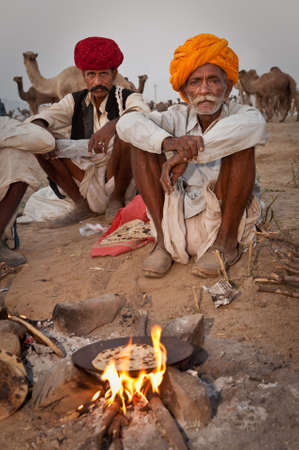 rajasthan: A group of rajasthani men baking chapati over a fire at the Pushkar Camel Fair 2009