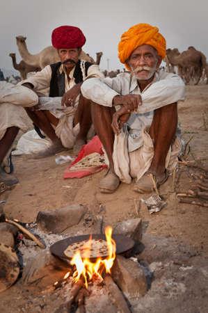 squatting: Un grupo de hombres de rajasthani hornear chapati sobre un incendio en el 2009 Feria de Camel Pushkar