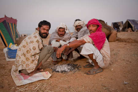 squalor: A group of rajasthani men huddling over the warm ashes on a crisp desert morning at the Pushkar Camel Fair 2009