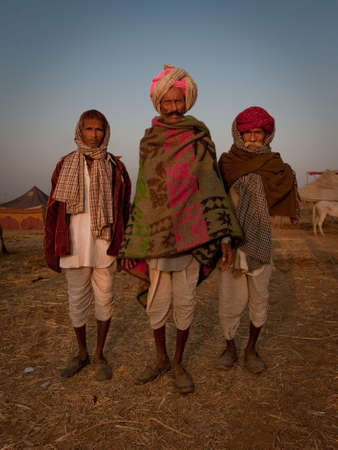 blanket horse: A group of three rajasthani men in the early sunlight at the Pushkar Camel Fair 2009 Editorial
