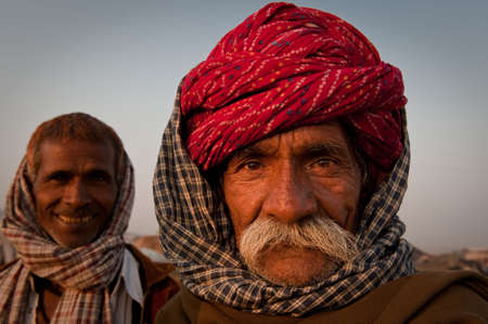 poverty in india: Headshot of two rajasthani men looking at the camera with a friendly expression at the Pushkar Camel Fair 2009