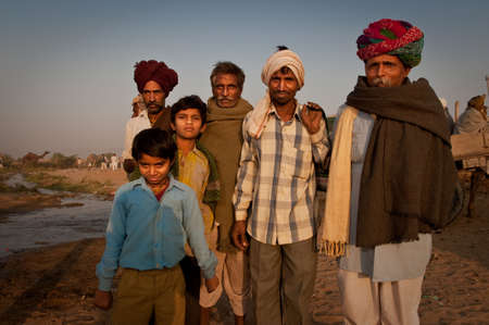 mixed age: A group of rajasthani males of mixed age standing near a creek at the Pushkar Camel Fair 2009 in the early morning sunlight.