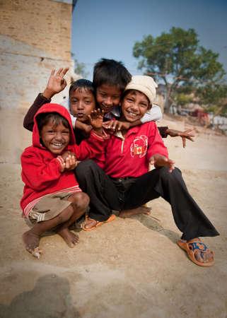 piedi nudi ragazzo: Un gruppo di quattro ragazzi divertirsi al Ghat del fiume Gange a Varanasi, India.