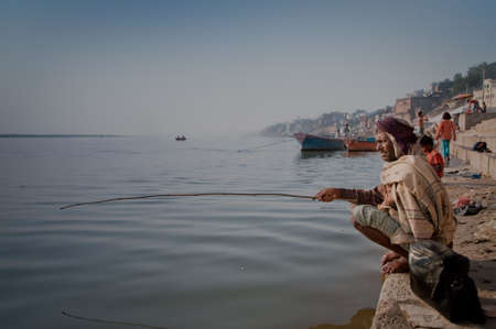 A man fishing at the heavily polluted Ganges river in Varanasi, India.