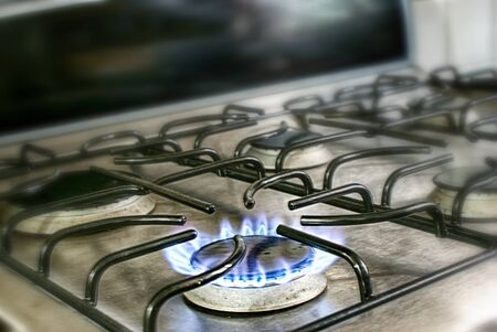stove fire: Photograph of a gas stove blue fire flame