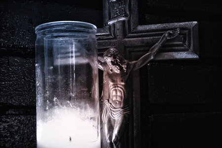 crucifix: Crucifix and wax lighted candle Stock Photo