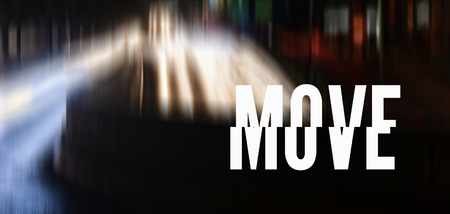 Photo of a street with car lights and the word MOVE in white and capital letters